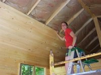 A customer installing the finished ceiling of a cabin kit built by bavariancottages.com and shipped to New York State