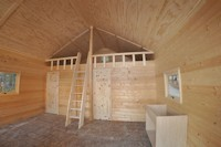 Inside the La Casa cabin kit showing the finished wood ceiling and cabin ready to have the kitchen installed